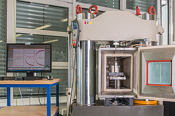 Servo-hydraulic testing machine for examining service life at high load frequencies