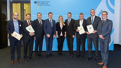 Nadine Magura, scientific assistant at IKV (centre), at the presentation of the notification of funding approval at the BMVI in Berlin. On her right, Steffen Bilger. On the left of the picture: Daniel Schneider, head of the Composites department at IKV