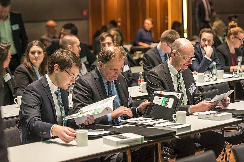 Teilnehmer nutzen das Informationsmaterial zur Tagung