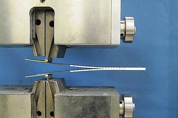 Universalprüfmaschine mit Vorrichtung, die den Verbund mit der typischen Weiterreißbelastung beaufschlagt