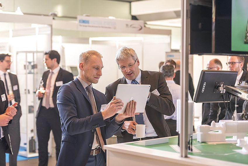 Besucher im Gespräch mit wissenschaftlichen Mitarbeitern am IKV-Satelliten Industrie 4.0