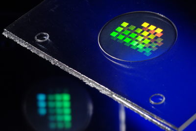 Injection molded plastic optics with microstructures