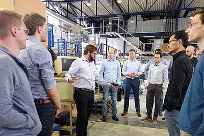 """Teilnehmer des Seminars """"Faserwickel- und Pultrusionsverfahren"""" bei der Praxisdemonstration im IKV Technikum"""