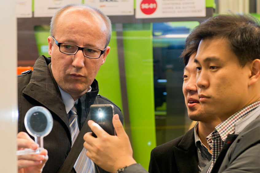 Visitors to the Polymer Optics Days examine injection-moulded lenses | Photo: IKV / Fröls