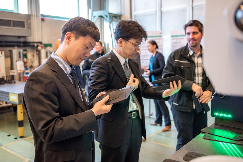 Teilnehmer der Konferenz verschaffen sich einen Eindruck von spritzgegossenen Probekörpern
